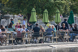 © Licensed to London News Pictures. 19/09/2020. London, UK. Drinkers enjoy the warm sunshine at a cafè next to the Serpentine as Police patrol Hyde Park in London on the first weekend of the Rule of Six where gatherings of over six people have now been banned by the Government after a spike in coronavirus cases. Prime Minister Boris Johnson announced yesterday that the UK was heading for a second wave with the North East already under lockdown.  Photo credit: Alex Lentati/LNP