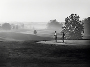 Two men golfing in the early morning as mist covers the course