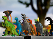 Toy dinosaurs lined up on a bench on 27th December 2016, Lagrasse, France. . Dinosaurs are a diverse group of animals of the clade Dinosauria. They first appeared during the Triassic period, 231.4 million years ago.