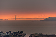 Looking west across San Francisco Bay at the Golden Gate Bridge in an orange haze of wildfire smoke near sunset, south of the Sonoma and Napa wildfires. Air quality on this day was rated as bad in San Francisco as in Beijing China. 12th October, 2017.