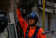 Chilean worker holds up fist ensuring crowd stays quiet so the team is able to trace signs of life underneath the rubble Thursday, 3 Aug 2020.(VXP Pictures/ Matt Kynaston)