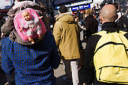 A child with a baby doll on her rucksack walks past a similarly bald-headed man.