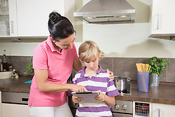 Woman with her son using digital tablet in kitchen, Bavaria, Germany