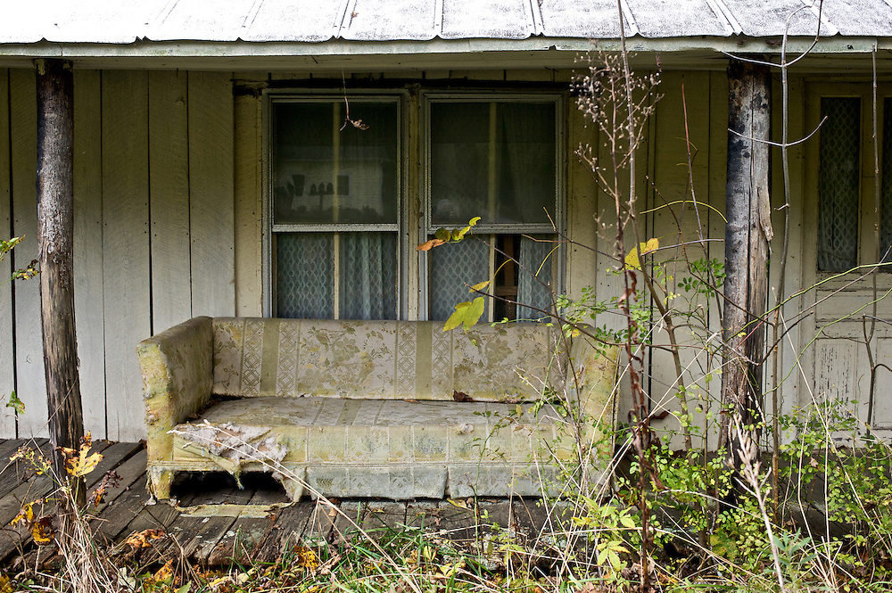 An old couch rests on the porch of an old home in the North Carolina Mountains