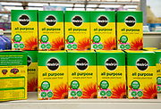 Cardboard boxes of Miracle-Grow all purpose soluble plant food on shelf display in garden centre, UK