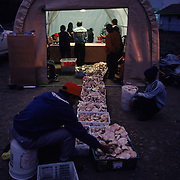 Matsutake mushroom pickers bring their harvests to buyers in Crescent Lake Junction, Oregon. Dozens of brokers in makeshift booths bargain with pickers over the best price per pound. Dollar amounts vary widely, depending on the quality of the mushroom and the demand of the Japanese market. A good picker can easily average several hundred dollars per day. In 1993, matsutake prices peaked at $600 per pound, but they normally average between $10 Ð 30.  At the nightly auction stations, as much as $6,000 in cash can change hands in an hour.