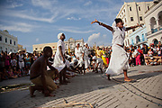 Cuban womn of African descent dancing, smiling as part of a performance. Performance in Havana old town, local dance and theatre group enacting the slave trade, colonial rule and how African religion and beliefs continuing, becoming what is now Santeria.