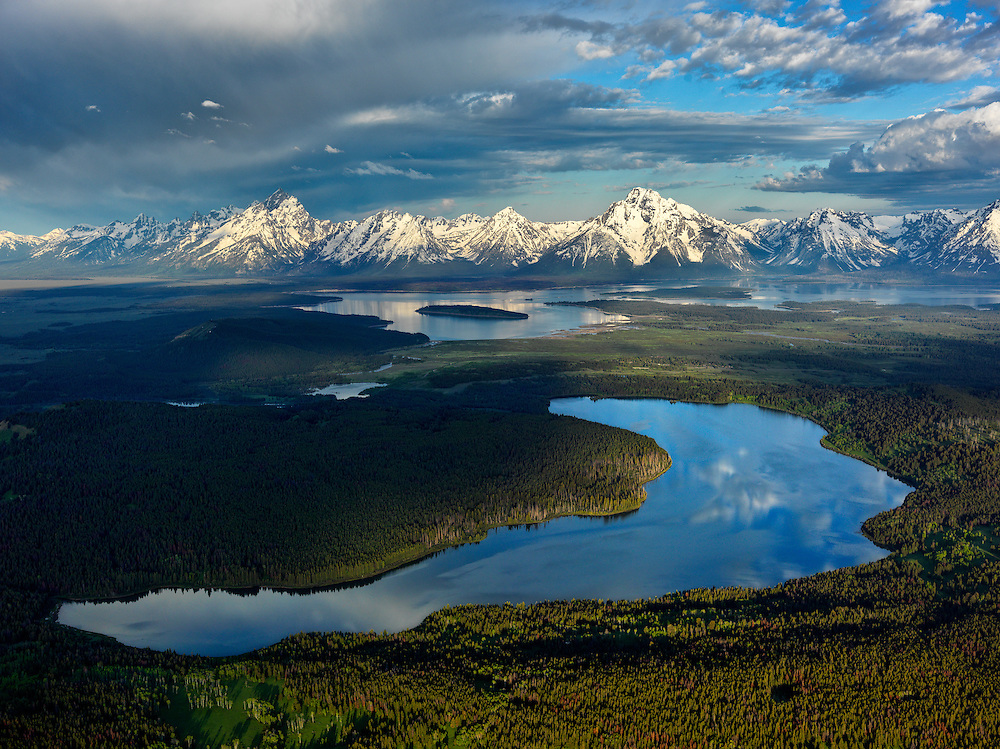 Aerial view of Emma Matilda Lake with Jackson Lake and snow capped Teton Mountain Range in the background in Teton National Park.<br /> Licensing and Open Edition Prints