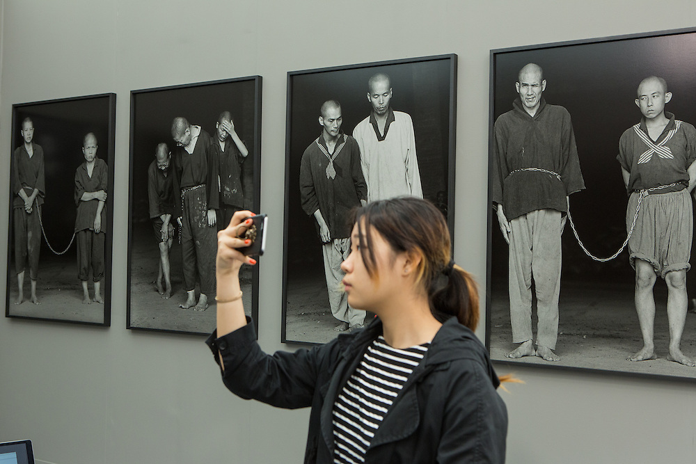 "New York, NY - 6 May 2016. Frieze New York art fair. A visitor among the large-scale silver-gelatin photos by Magnum photogra[her Chien-Chi Chang, from his series ""The Chain"", in the Chi-Wen Gallery of Taipei."
