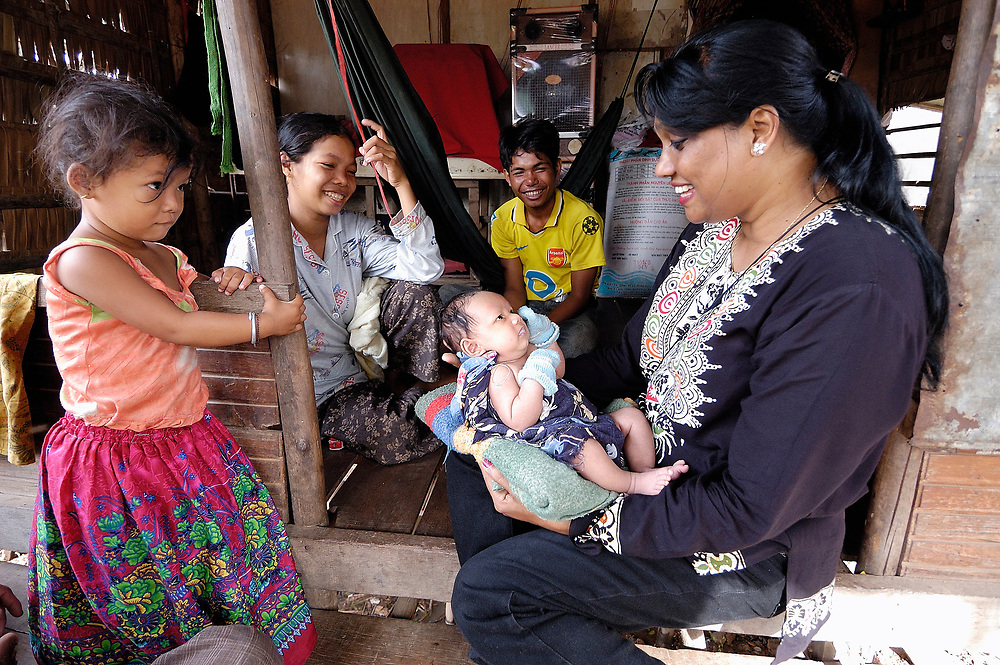 Clara Biswas (right), a United Methodist missionary who works with women and children and youth in the Cambodian capital of Phnom Penh, visiting and talking with people in the Deumkor neighborhood of the city. Biswas is from Bangladesh.