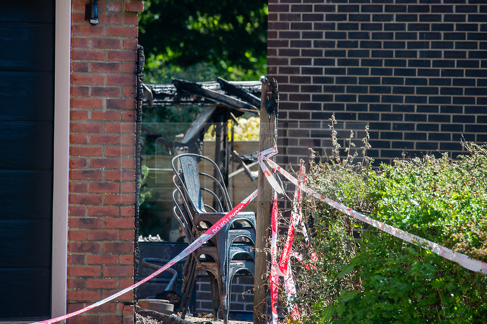 © Licensed to London News Pictures. 06/05/2020. Woolton Hill, UK. Red tape marks a cordon, in the background are several chairs and a fire damaged structure at the rear of a house destroyed by fire.  A fire has destroyed two houses on Woolton Lodge Gardens, Woolton Hill in Hampshire. The fire started approximately 20:10 BST on Tuesday 05/05/2020. Photo credit: Peter Manning/LNP
