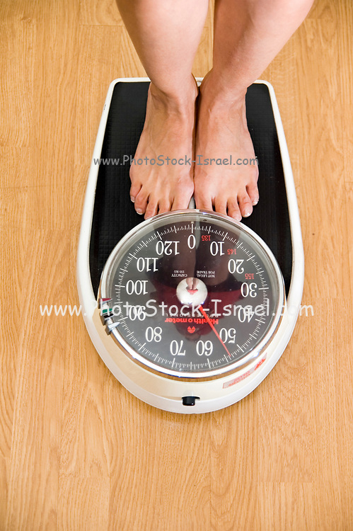 Bare feet of a woman standing on a scale on a wooden floor