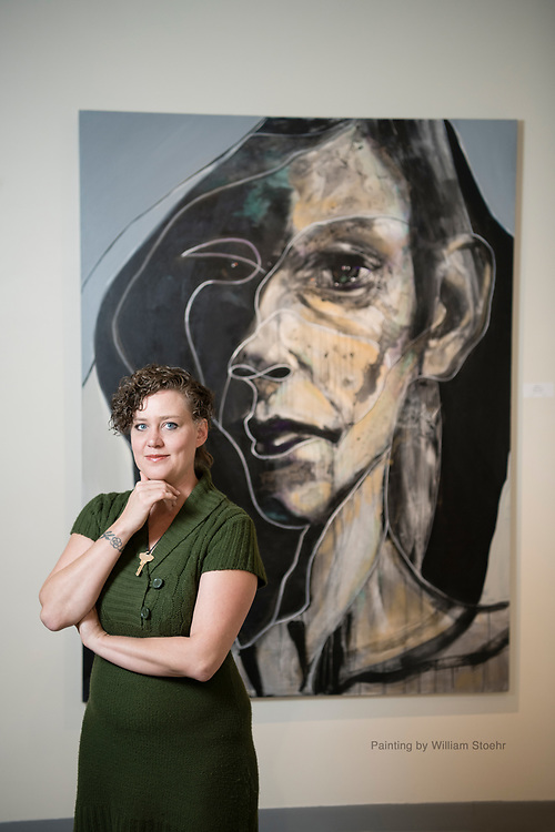 Portrait of the director of the Dairy Center for the Arts in Boulder Colorado standing in front of a painting.