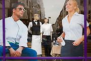 Stylish mannequins and illustrations of staff wearing uniforms in a Soho street. Seen through the window of a shop selling outfits for the catering and restaurant industry workplace, the models of good-looking young working people (a waitress and waiter, chef and kitchen staff) occupy a prominent position in this Soho street in central London.