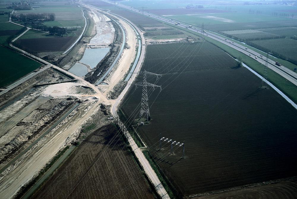 Nederland, Gelderland, Valburg -Elst, 04-04-2002; aanleg Betuweroute, met rechts autosnelweg A15; naast de goederenspoorlijn zelf zou in de toekomst op deze lokatie het multimodaal transport centrum gebouwd moeten worden. Dit omstreden MTC zou moeten dienen voor overslag van spoor naar vrachtauto's; en  overslag naar binnenvaartschepen (rivier de Waal rechts van de A15, net buiten beeld, in di gebied rechtsheeft Milieudefensie een boomgaard aangekocht om de ontwikkleingen tegen te werken); vrachtvervoer verkeer en vervoer milieu .Deel van een serie over Betuweroute / infrastructuur.<br /> luchtfoto (toeslag), aerial photo (additional fee)<br /> photo/foto Siebe Swart