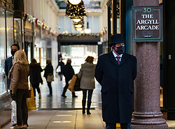 Glasgow, Scotland, UK. 11 December 2020. Covid-19 lockdown level 4 restrictions are lifted in Glasgow. Non essential businesses such as shops and restaurants can reopen from today. Pictured ; Concierge stands outside re-opened Argyll Arcade jewellers shopping arcade on Buchanan Street.  Iain Masterton/Alamy Live News