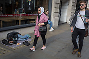 Passers-by walk past sleeping man on pavement, on 30th March 2017, in London, England.