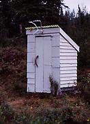 Little white outhouse at the Caribou Creek Cabin, Talkeetna Mountains, Alaska.