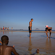 Locals play football in the late afternoon light at Sao Conrado beach, Rio de Janeiro,  Brazil. 8th July 2010. Photo Tim Clayton..The beaches of Rio de Janeiro, provide the ultimate playground for locals and tourists alike. Beach activity is in abundance as beach volley ball, football and a hybrid of the two, foot volley, are played day and night along the length and breadth of Rio's beaches. .Volleyball nets and football posts stretch along the cities coastline and are a hive of activity particularly at it's most famous beaches Copacabana and Ipanema. .The warm waters of the Atlantic Ocean provide the ideal conditions for a variety of water sports. Walkways along the edge of the beaches along with exercise stations and cycleways encourage sporting activity, even an outdoor gym is available at the Parque Do Arpoador overlooking the ocean. .On Sunday's the main roads along the beaches of Copacabana, Leblon and Ipanema are closed to traffic bringing out thousands of people of all ages to walk, run, jog, ride, skateboard and cycle more than 10 km of beachside roadway. .This sports mad city is about to become a worldwide sporting focus as they play host to the world's biggest sporting events with Brazil hosting the next Fifa World Cup in 2014 and Rio de Janeiro hosting the Olympic Games in 2016...