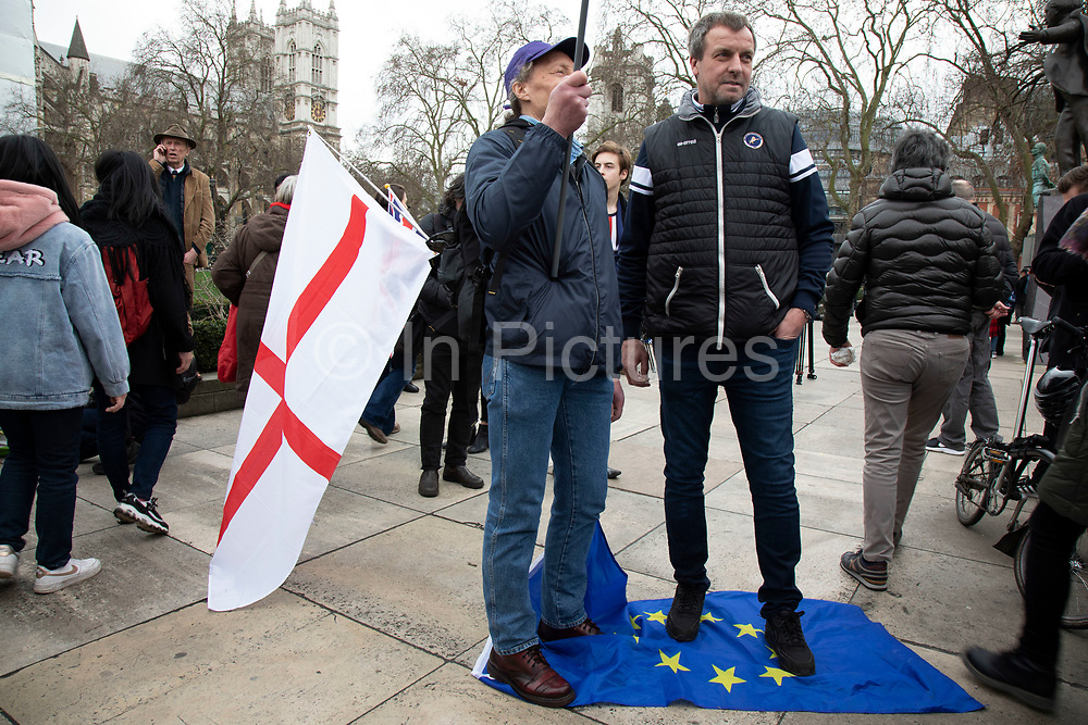Pro Brexit Leave supporters standing on an EU flag as they gather in Westminster on Brexit Day as the UK prepares to leave the European Union on 31st January 2020 in London, England, United Kingdom. At 11pm on Friday 31st January 2020, The UK and N. Ireland will officially leave the EU and go into a state of negotiations as to the future arrangement and trade agreement, while adhering to EU rules until the end of 2020.