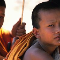 Young monks sit under umbrella, Ban Pak Ou, Luang Phrabang, Laos