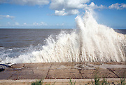 Waves hit sea wall illustrating hydraulic action and corrasion coastal erosion, East Lane, Bawdsey, Suffolk