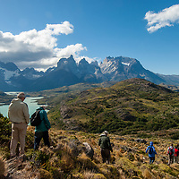Hikers descend a hill above Lake Pehoe and the Towers of Paine, Torres del Paine National Park, Chile.