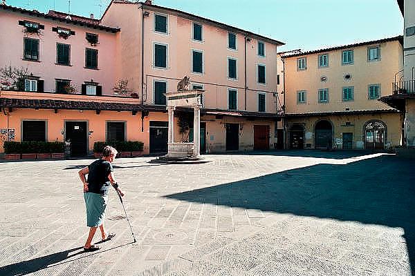 Italie, Toscane, 25-8 2001Oudere vrouw loopt op een pleintje in een stadje.Elderly woman walks on a little square in a small town.Foto: Flip Franssen