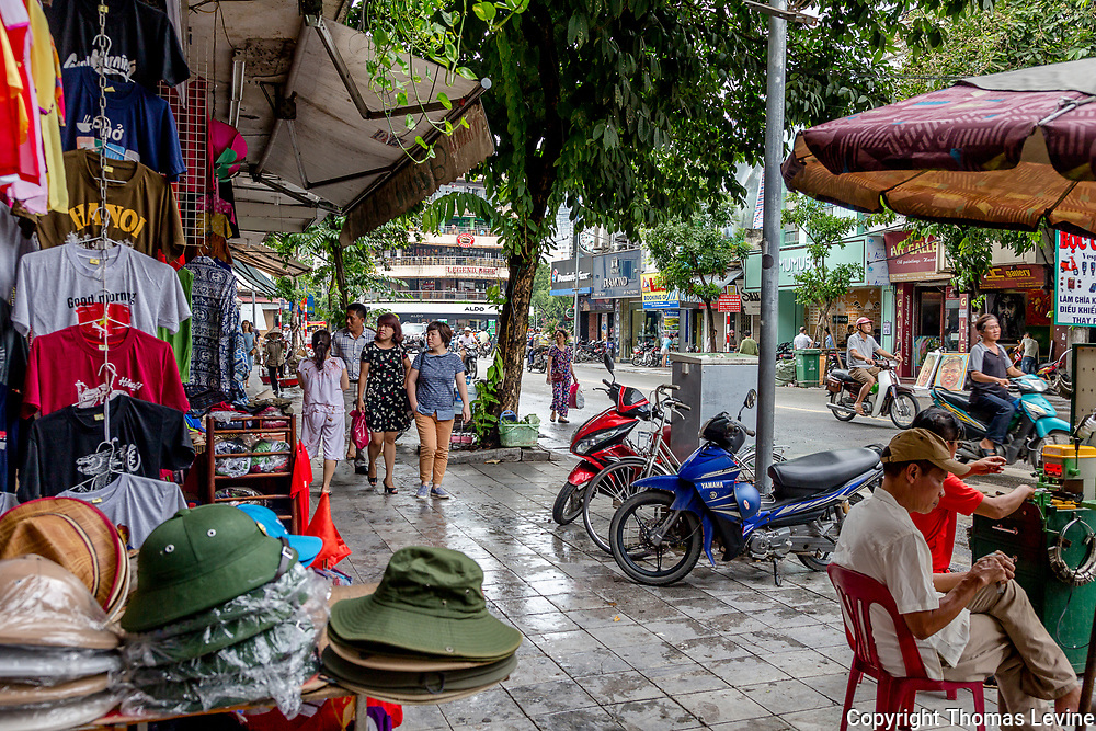 Shopping in the Old Quarter in Hanoi, Vietnam. Rain soaked sidewalks and people walking.