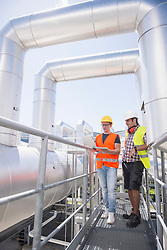 Engineer and worker in meeting with laptop at geothermal power station, Bavaria, Germany