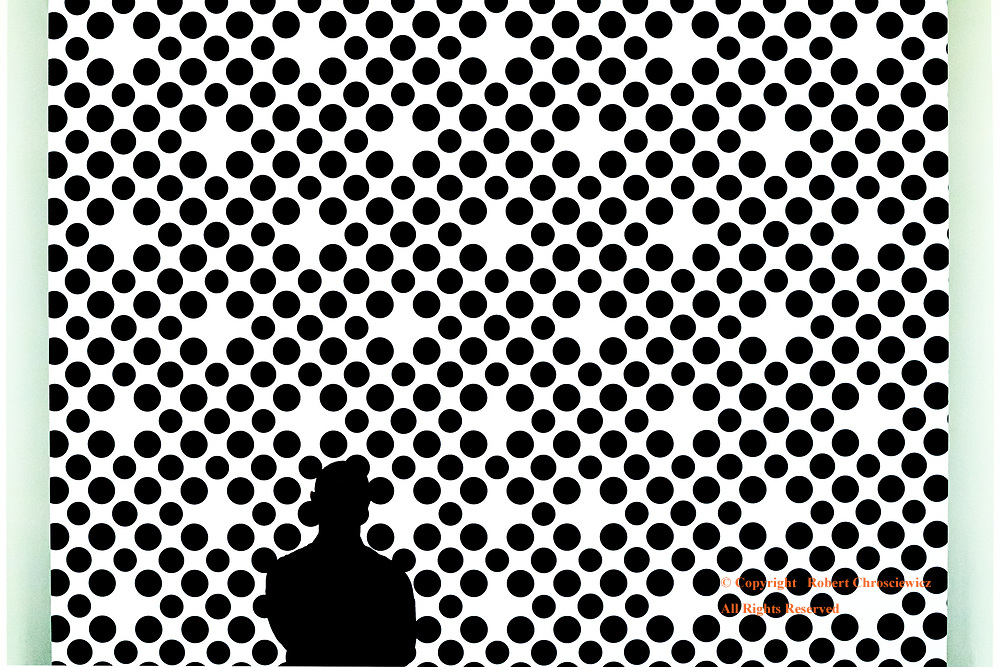 Contrast in Silhouette: The silhouette of a man held within the art work of circles, Vancouver Art Gallery, Vancouver British Columbia Canada.