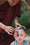 Young novice Monk having his head shaven with accepting look and eyes closed