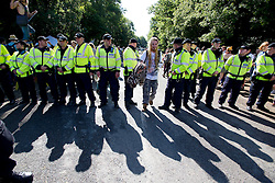 © London News Pictures. 19/08/2013. Balcombe, UK. An Activist passes peacefully through a police cordon outside the Cuadrilla drilling site in Balcombe, West Sussex on a day of of civil disobedience organised by campaign group No Dash For Gas. Cuadrilla has temporarily ceased drilling at the site, which has been earmarked for fracking, under advice from the police. Photo credit: Ben Cawthra/LNP