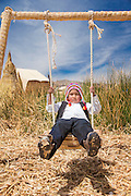 Child playing on swing at School on the Floating islands of Lake Titicaka, Puno, Peru, South America