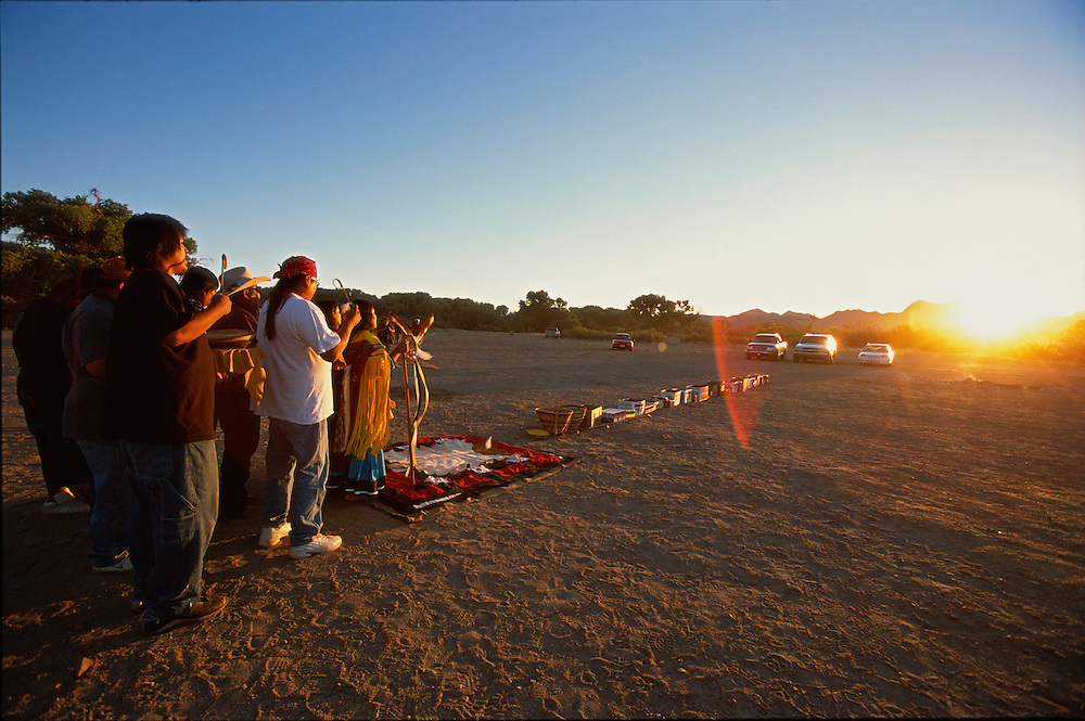 Apache Indians dance at a Sunrise Dance, the first menstruation ceremony of an Apache girl, on the San Carlos Apache Reservation, Arizona, USA. Behind the girl, who is dressed in buckskin clothes, the medicine man and his helpers sing and beat their drums. The long row of cartons filled with snacks and drinks, in front of the girl, symbolises a life without material want. The rites are supposed to prepare the girl for adulthood and to give her a long and healthy life. During the rites the girl also becomes Changing Woman, a mythical female figure, and comes into possession of her healing powers.