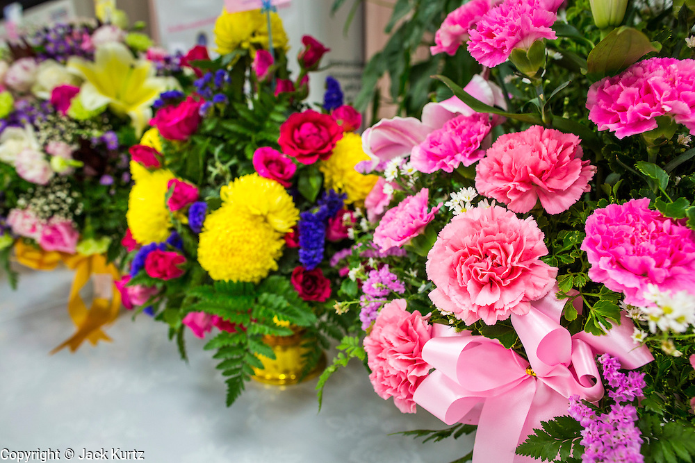26 NOVEMBER 2012 - BANGKOK, THAILAND: Pink and yellow flowers left for the hospitalized King of Thailand at Siriraj Hospital in Bangkok. Yellow and pink are preferred colors for flowers because yellow is the color of the monarchy and pink is viewed as a fortuitous color that could bring the King better health. Siriraj was the first hospital in Thailand and was founded by King Chulalongkorn in 1888. It is named after the king's 18-month old son, Prince Siriraj Kakuttaphan, who had died from dysentery a year before the opening of the hospital. It's reported to one of the best hospitals in Thailand and has been home to Bhumibol Adulyadej, the King of Thailand, since 2009, when he was hospitalized to treat several ailments. Since his hospitalization tens of thousands of people have come to pay respects and offer get well wishes. The King's 85th birthday is on Dec 5 and crowds at the hospital are growing as his birthday approaches. The King is much revered throughout Thailand and is seen as unifying force in the politically fractured country.        PHOTO BY JACK KURTZ