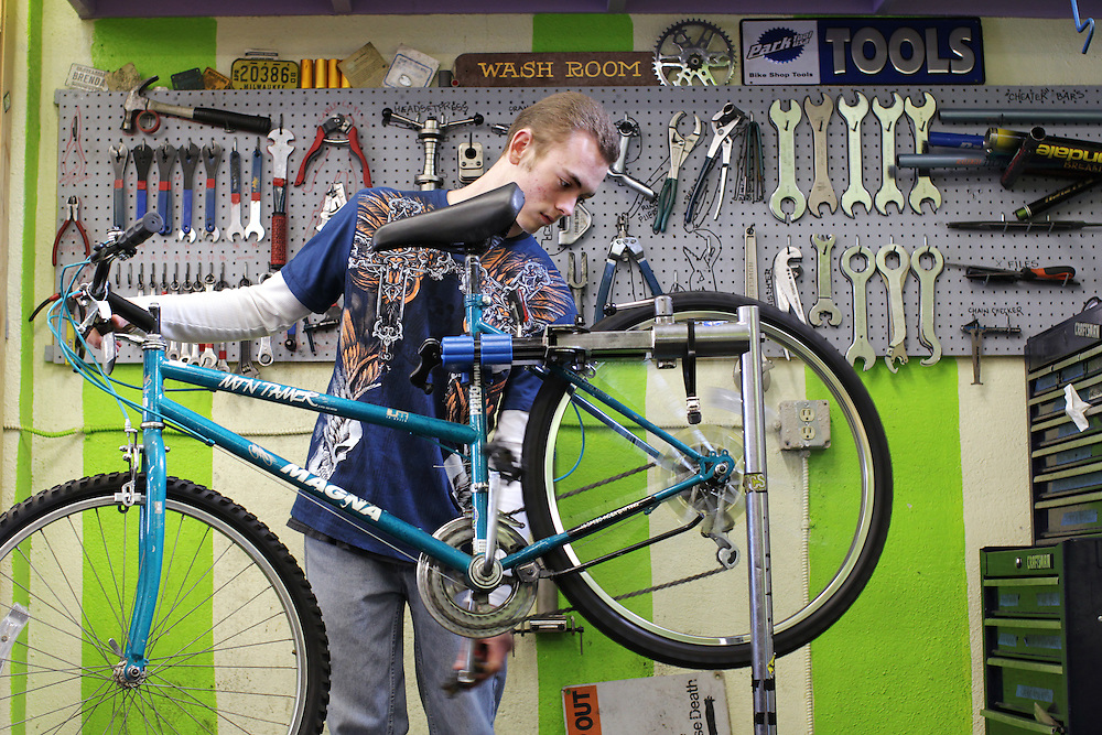 Youth Express apprentice Taylor Altendorfer, 16, fixes the brakes on a donated bicycle at Express Bike Shop in St. Paul, Minnesota.  By refurbishing and selling bicycles, youth apprentices learn mechanical, business, and entrepreneurial skills.