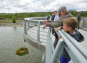 """Lou Hochheiser drops a wreath into the Snake River on Monday as American Legion Post 43 holds a Memorial Day ceremony on the pathways bridge, saluting those who made the ultimate sacrifice in service of the armed forces. Hochheiser was a submariner and Marine in Vietnam until 1968. """"It's a remembrance of the guys we lost when I was over there,"""" Hochheiser said."""