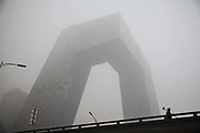 A man holding a monitoring device stands in front of the China Central Television CCTV headquarters building shrouded in haze in  Beijing, China, on Monday, Nov. 30, 2015.  China has made a concerted effort to cut down pollution, especially in the nation capital, however there are still heavily polluted days especially in the winter months.