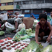 A man sleeps as the sunrises in an early morning scene on October 9, 2008 at Divasoria markets, Manila, the Philippines. Photo Tim Clayton