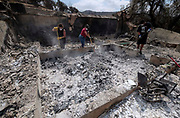 Friends of home owner, survey the charred debris left in a burned out home, Monday, Sept. 4, 2017, in the Sunland-Tujunga of Los Angeles, the United States, on Sept. 4, 2017. More than 1,000 firefighters work for a fourth day to put out a 7,000-acre brushfire that is 30 percent contained, as the last of the residents ordered to evacuate the record-setting blaze were expected to<br /> return to their homes authorities said. (Xinhua/Zhao Hanrong)(Photo by Ringo Chiu)<br /> <br /> Usage Notes: This content is intended for editorial use only. For other uses, additional clearances may be required.