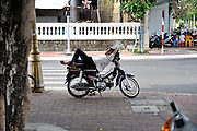 """It is customary in Vietnam for people to have a """"siesta"""" type break in the middle of the day, including a nap if possible. A young man taking a nap on his motorbike, Vung Tau, Vietnam"""