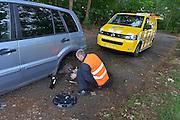 Nederland, Lichtenvoorde, 20-6-2015Een medewerker van de ANWB helpt een automobilist die op een parkeerplaats staat met speling op het wiellager. Hij weet het euvel te provisorisch te herstellen zodat de auto zijn reis kan vervolgen. Wel moet hij snel het lager bij de garage laten vervangen.FOTO: FLIP FRANSSEN/ HOLLANDSE HOOGTE