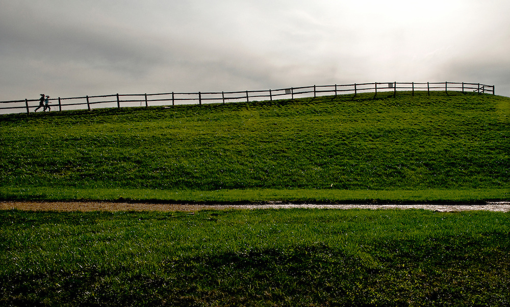 A pair of runners make their way up a large hill at Bicentennial Park in Grand Blanc on an overcast day.