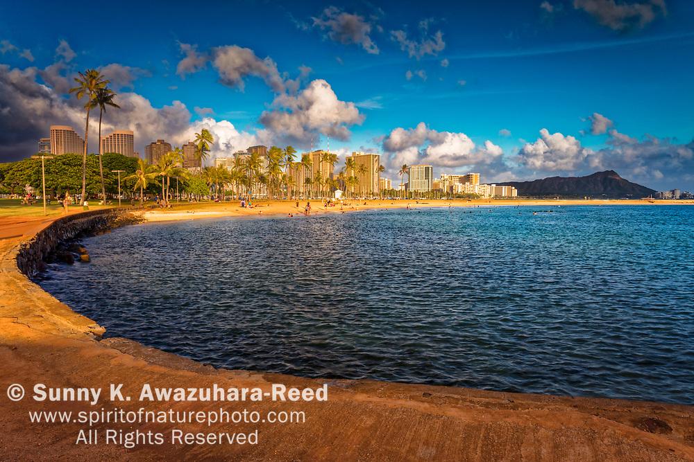 Magic Island Beach under blue sky. Waikiki skyline and Diamond Head in the background. Honolulu, Oahu Island, Hawaii.