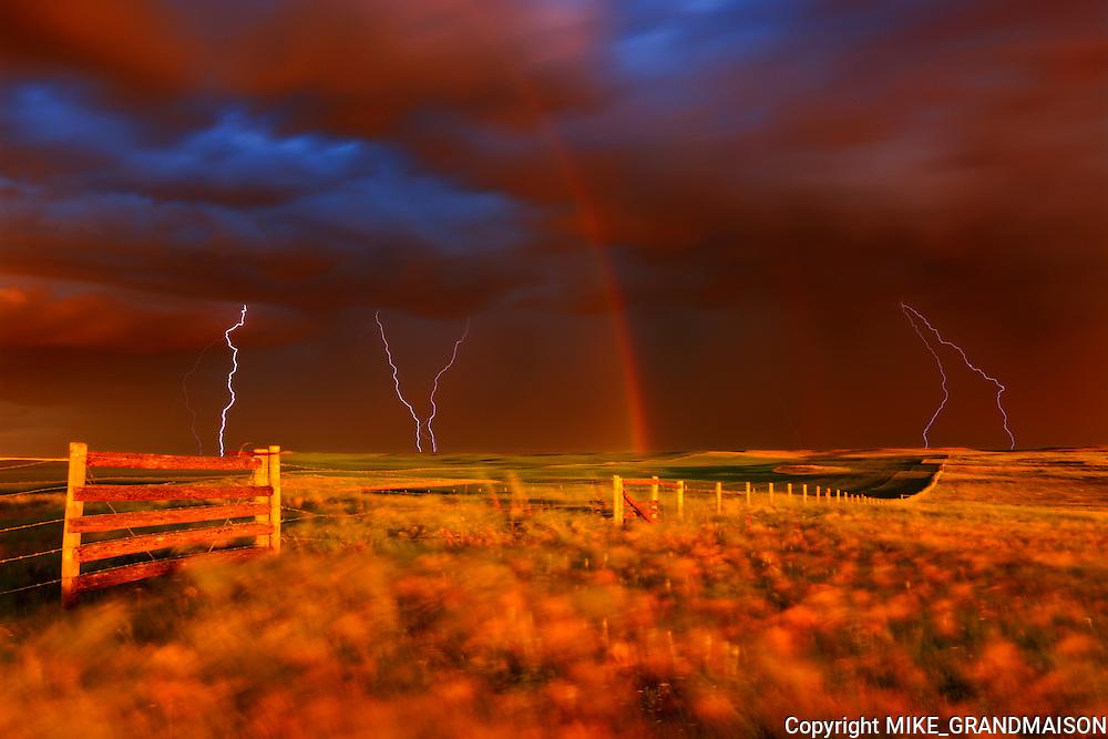 Lightning strikes, rainbow and setting sun during prairie storm. West Block<br /> Grasslands National Park<br /> Saskacthewan<br /> Canada