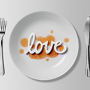 A photographic illustrating a love for food by spelling out the word 'love' on a plate of orange sauce.