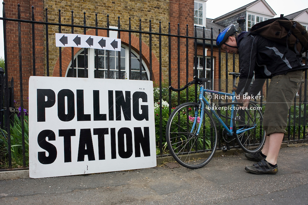 A cyclist locks his bike on to railings at St. Saviour's Church, Herne Hill SE24 that serves as a temporary Polling station for voters on Britain's general election day.