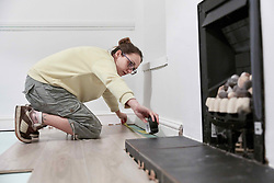 February 14, 2018 - Woman measuring space fit new floor boards (Credit Image: © Mint Images via ZUMA Wire)