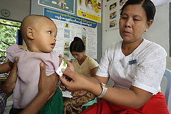 Maw Maw San (30)  mother  Maw Maw Naing ( 5 months) visits the clinic where  Daw Toke Toke is the midwife.  They are checked for malnutrition by using the UNICEF approved method of growth monitoring.  Laputtaloke Taung village close to Lamputta, Myanmar.